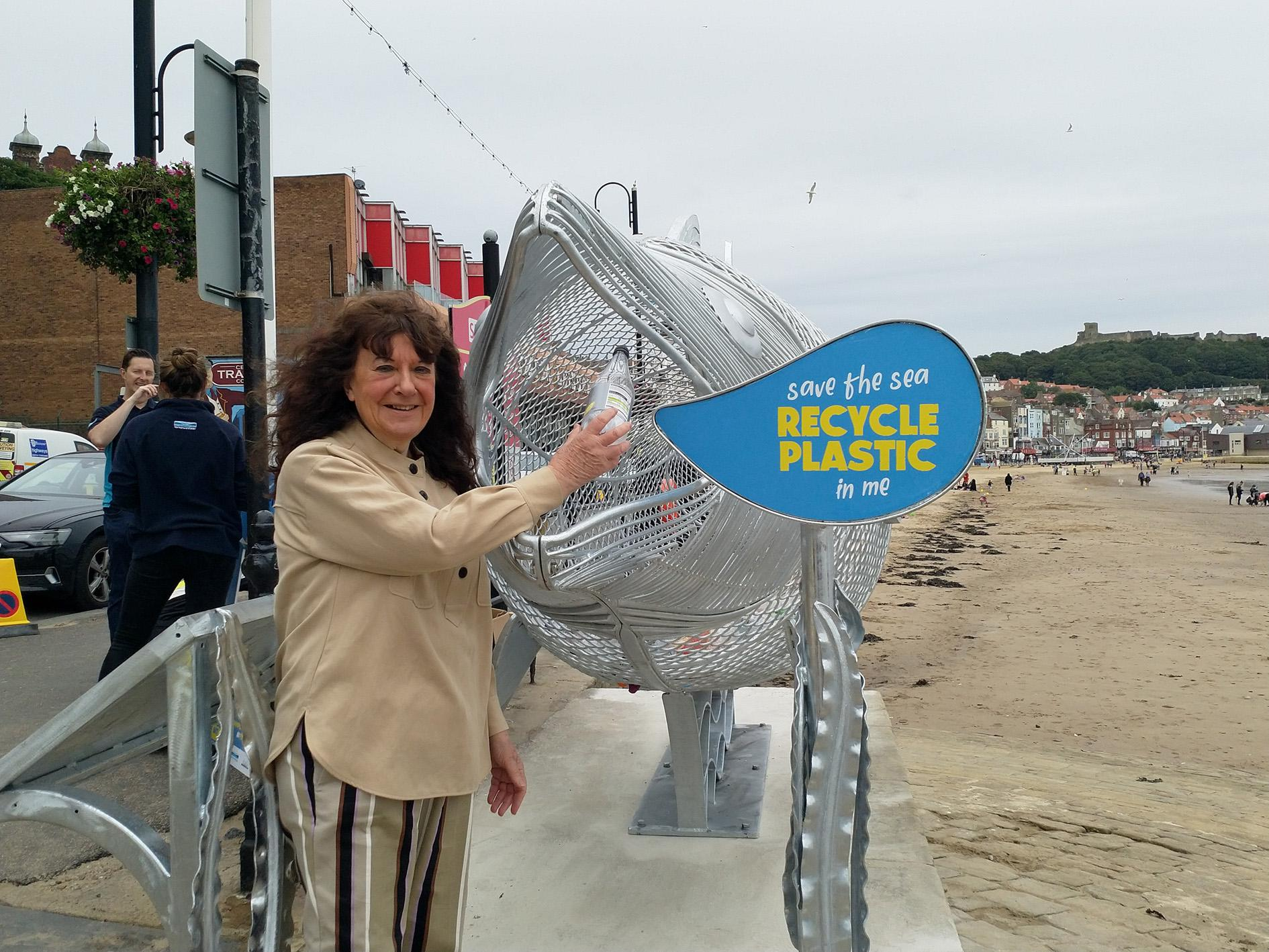 Picture of Cllr Janet Jefferson feeding the Fin the Fish sculpture with a single use plastic bottle