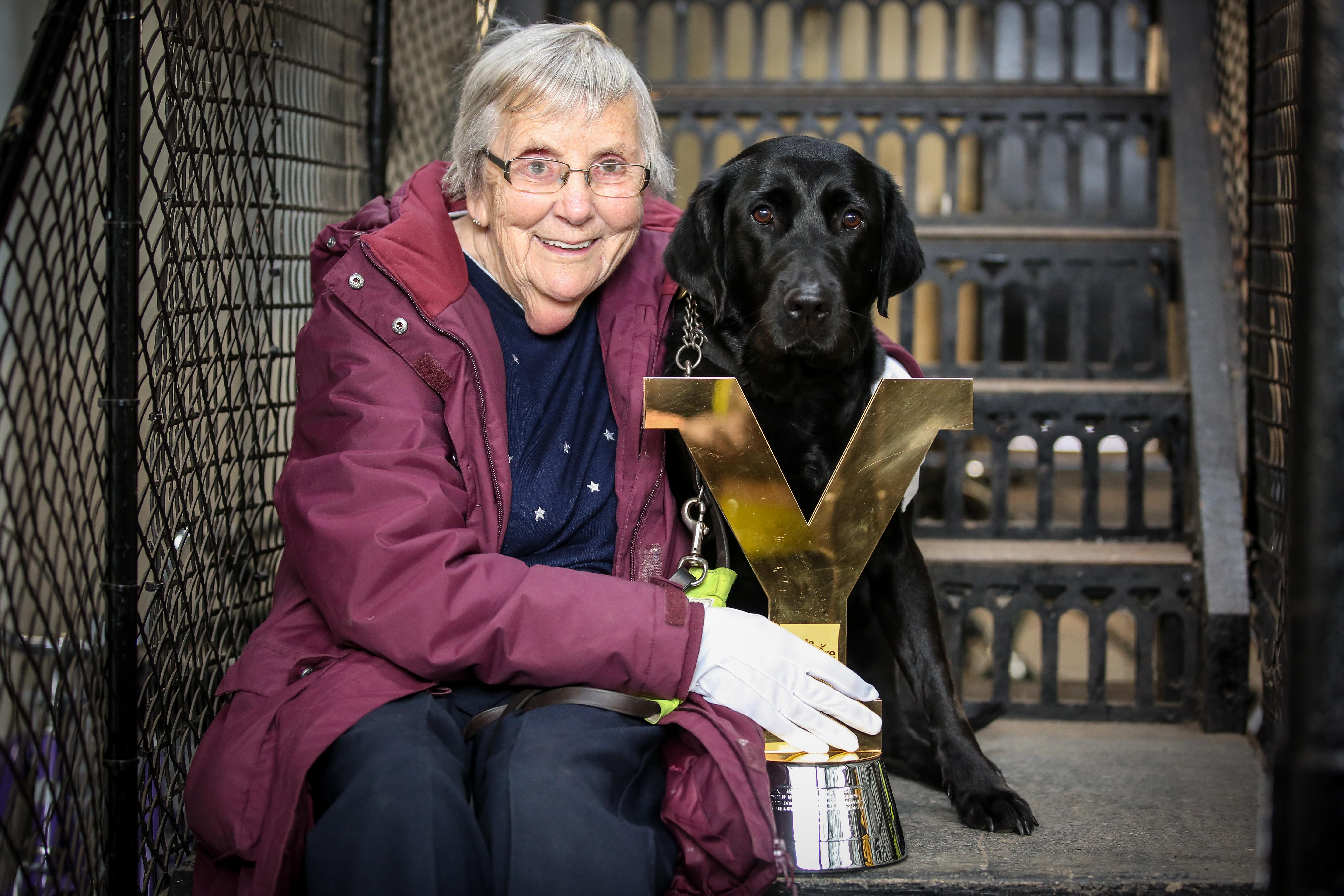 Picture of 82 year-old Alice Wilson, a regular user of Scarborough's Yorkshire Bank Bike Library, with the Tour de Yorkshire trophy, accompanied by her guide dog, Quaver. Picture credit: Ceri Oakes Photography