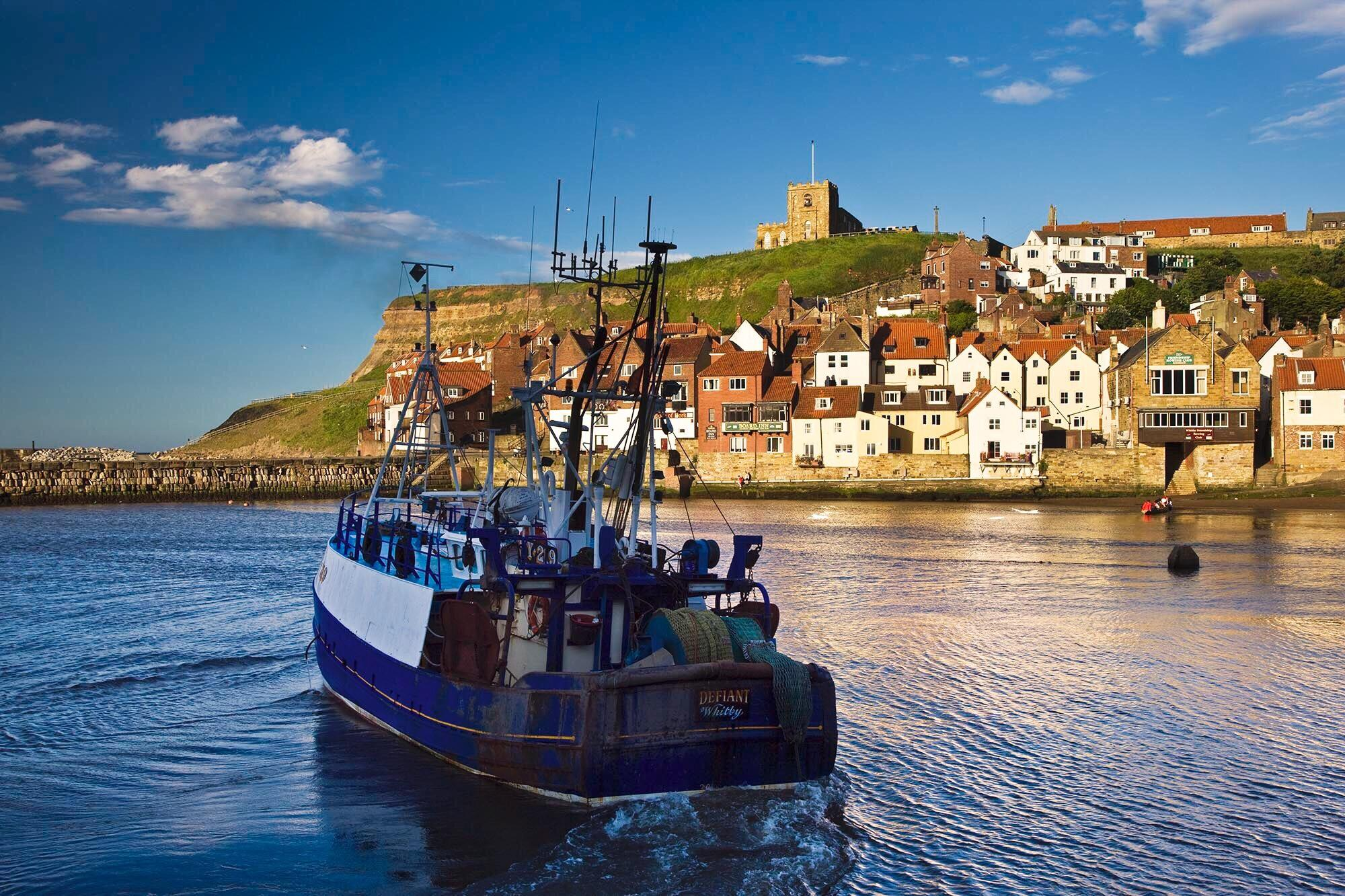 Picture of a boat leaving Whitby harbour against the backdrop of St Mary's Church and the east cliff
